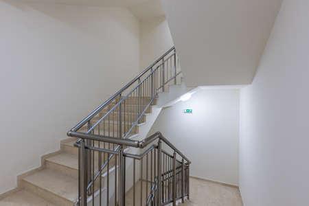 Modern stair case between floors. Stairs with metallic rail in modern building Stock Photo