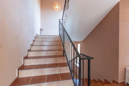 Modern stair case between floors. Stairs with metallic rail in modern building Standard-Bild