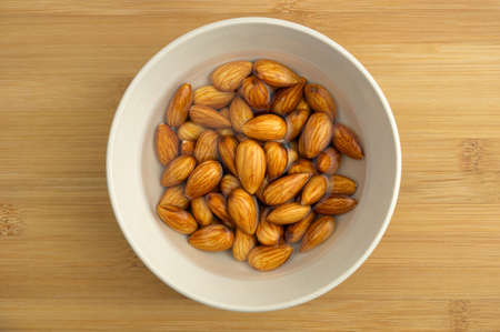 soaking: Activated almonds soaking in white bowl