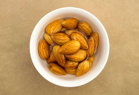 soaking: Raw almonds soaking in a white bowl of water