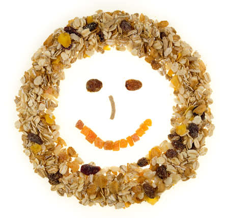 Breakfast cereal and muesli shaped in a happy face against a white background photo