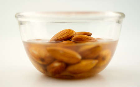 Almonds being soaked in a clear bowl, isolated on white Stock Photo