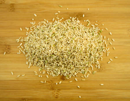 wholemeal: Uncooked brown rice pile on a wooden board