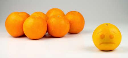 Sad orange ostracized by darker, taller oranges. photo