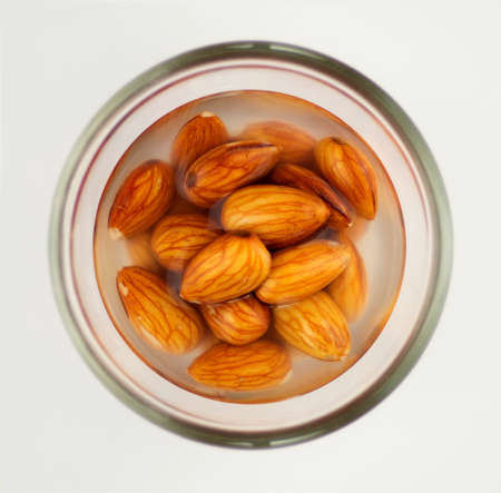 soaking: Closeup of raw almonds soaking in a glass bowl of water, isolated on a white background