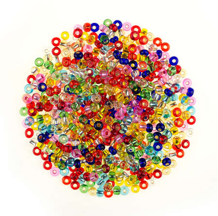 Round pile of coloured glass beads for DIY jewelry making, isolated on a white background