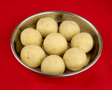 red tablecloth: Indian laddoo (laddu) sweets served on silver plate sitting on a red tablecloth.