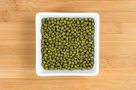 munggo: Green mung beans in white bowl on wooden board Stock Photo