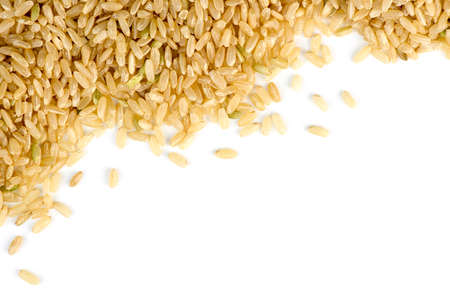 Brown rice scattered against white with copyspace