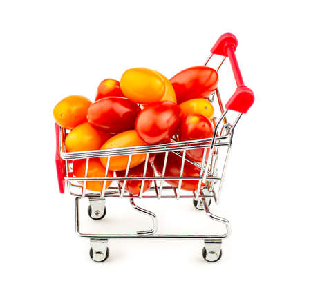 Colorful bunch of small grape tomatoes in shopping trolley isolated on white photo