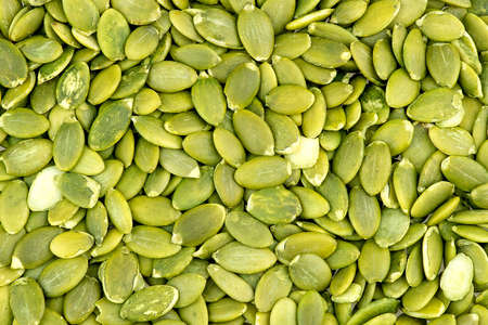 seed: Macro background texture of green pumpkin seeds