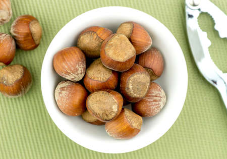 nut cracker: Natural hazelnuts in bowl with nut cracker aerial