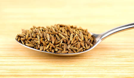 spoonful: Spoonful of cumin seeds against wooden background Stock Photo