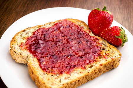 wheat toast: Macro closeup of delicious strawberry jam on whole wheat toast