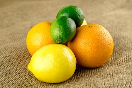 hessian bag: Limes, oranges and lemons in pile on farm fresh hessian bag Stock Photo