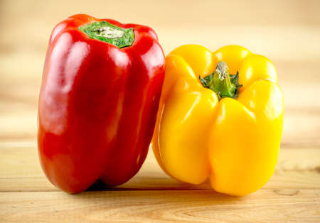 capsicum: Colorful, vibrant red and yellow capsicum on wooden chopping block