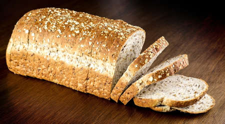 multi grain sandwich: Fresh whole wheat bread against wooden background Stock Photo