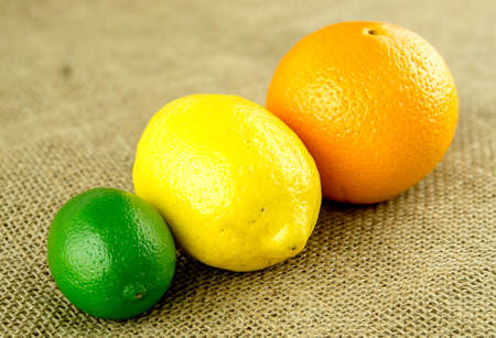 hessian: Orange, lemon and lime on hessian backdrop Stock Photo