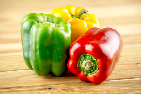 pimiento: Red yellow and green peppers on wooden background