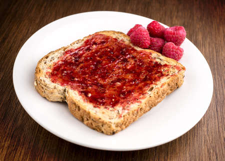 wheat toast: Tasty rasberry jam spread on whole wheat toast