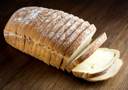 Loaf of white bread against wooden background Imagens