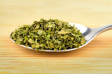 heaped: Heaped spoonful of dried parsley leaves