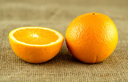 cross section: Perfect orange with cross section against rustic burlap hessian background Stock Photo