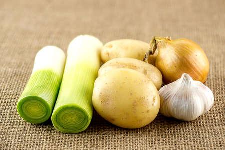 onion slice: Fresh garlic, potato, leek and onion on burlap sack Stock Photo