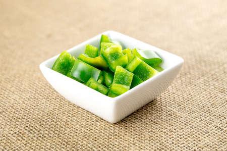 picada: Pimiento verde cortado en el fondo de arpillera orgánica