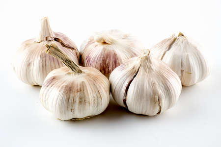 Purplish garlic heads with crackling skin isolated on white Stock fotó