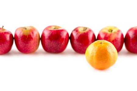 Single orange infront of line of apples