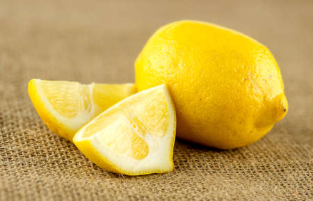 pulpy: Macro of pulpy wedges of lemon next to whole fruit