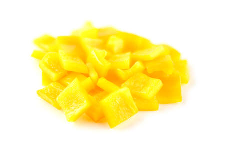 Crunchy cubes of diced yellow capsicum vegetable on white