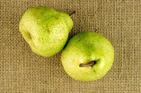 Ripe crispy green pears against hessian beckground