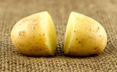 Macro of two halves of fresh potatoe on hessian