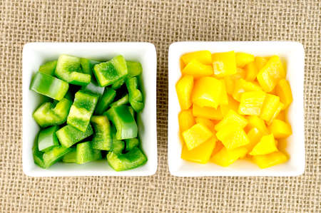 Green and yellow vegetarian pepper vegetables in square containers Imagens