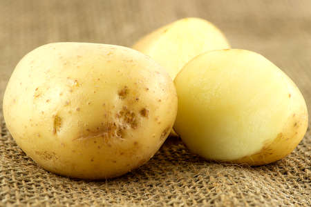 potatoe: Macro of whole unpeeled potatoe next to cut pieces