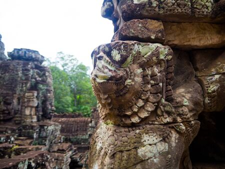Enigmatic giant stone faces of ancient Bayon temple in Angkor Thom, Siem Reap, Cambodia.