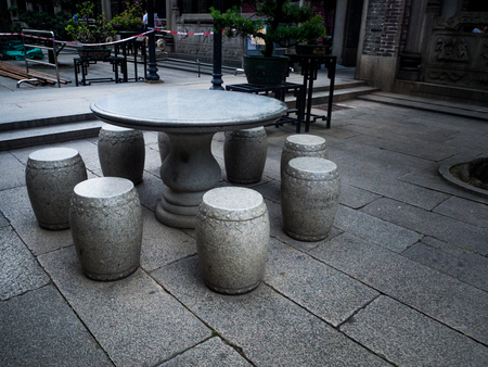 dining table and chairs: table and benches made of stone in the garden. chinese style.