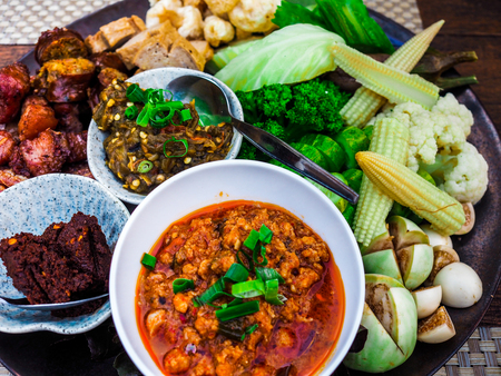 Thai food - Northern style dips with northern thai spicy sausage (sai oua), fried pork skin and Vetgetable Set. Stock Photo