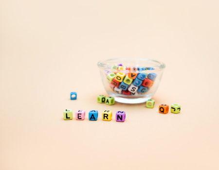Learn : Colorful cube letters  Glass cup on orange Background.