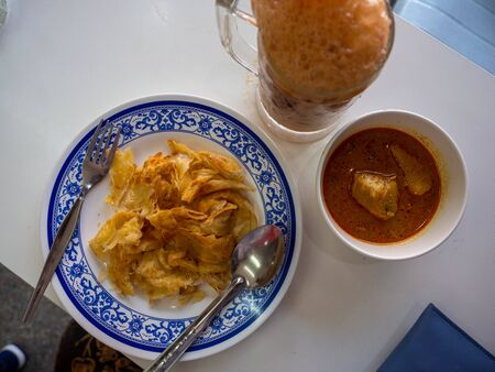 Thai tea and Roti with curry sauce in Thalang road at Phuket. Old Town. Phuket, Thailand. March 2019