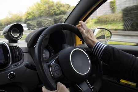 A man who smokes cigarettes while driving a car 写真素材
