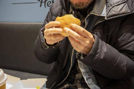 Man eating hamburger in restaurant Reklamní fotografie