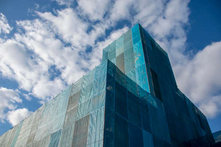 Building covered with blue sheet under construction