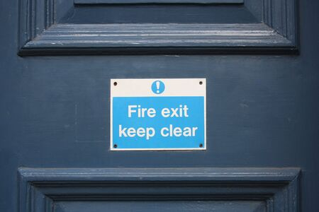 fire exit sign: Fire Exit Sign on a Wooden Door