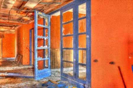 industrial wasteland: blue door with brocken windows in a orange corridor