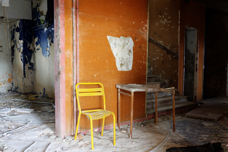 condemned: a yellow chair and a table in a orange corridor Stock Photo