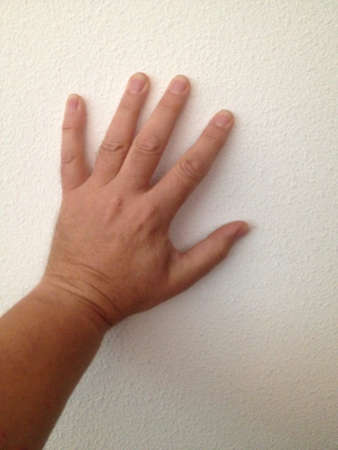 left hand: Left hand against wall Stock Photo