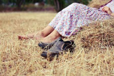 rests: Woman rests near a haystack